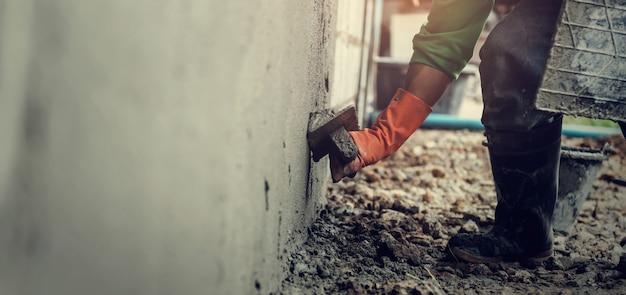 Крупным планом ручной работник штукатурка цемента на стене для строительства дома Premium Фотографии