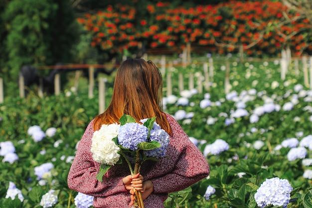 立っている女性庭のアジサイの花に向きを変えます Premium写真