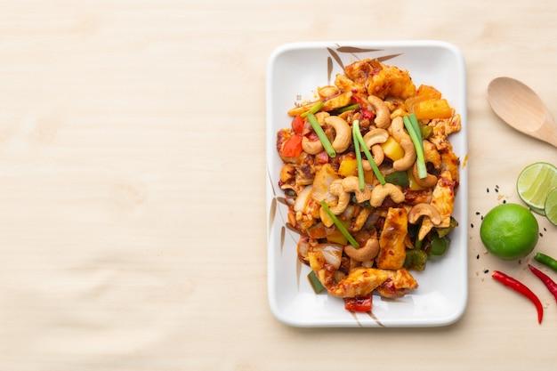 木製テーブルの上の皿にカシューナッツとフライドチキンをかき混ぜる Premium写真