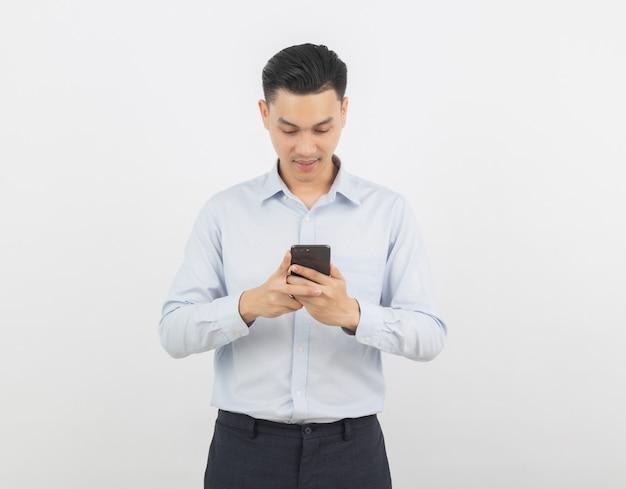 Азиатский бизнесмен играет на смартфоне с улыбкой на белом фоне Premium Фотографии