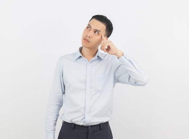 Молодой красивый азиатский бизнесмен думая идея пока смотрящ вверх Premium Фотографии