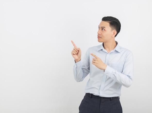 白で隔離される製品を提示する指で側を指している青いシャツと若いアジアビジネス男 Premium写真