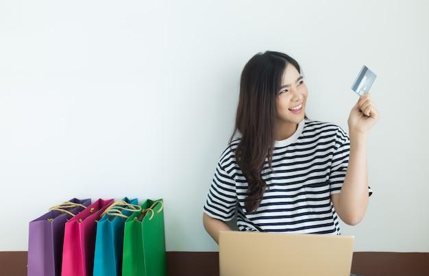 彼女のラップトップとショッピングバッグでクレジットカードを見ている若いアジアの女性。オンラインショップ Premium写真