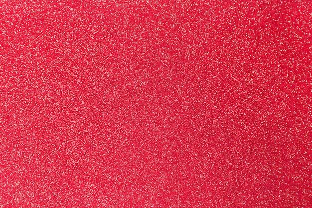 クリスマス、お祝いのコンセプトのための赤いキラキラ光沢のある質感。 Premium写真