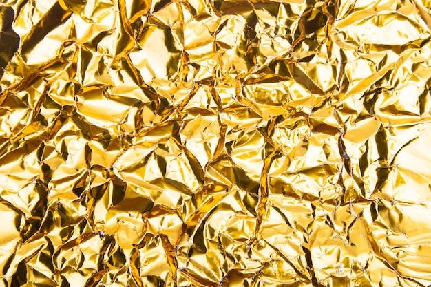 ゴールドのしわくちゃの箔紙のテクスチャ。 Premium写真