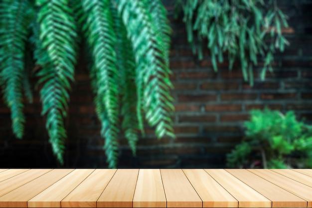壁に緑の木々。背景をぼかした写真の前に空のテーブルを木の板。 Premium写真
