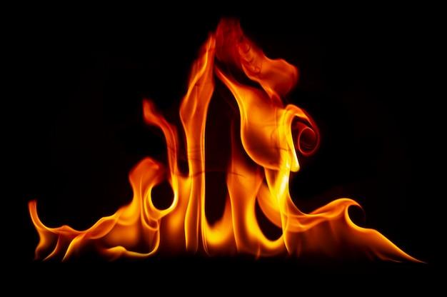 黒の背景に火の炎。心の熱い刺激 Premium写真