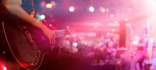 背景、柔らかい、ぼかしのコンセプトのためのステージ上のギタリスト Premium写真