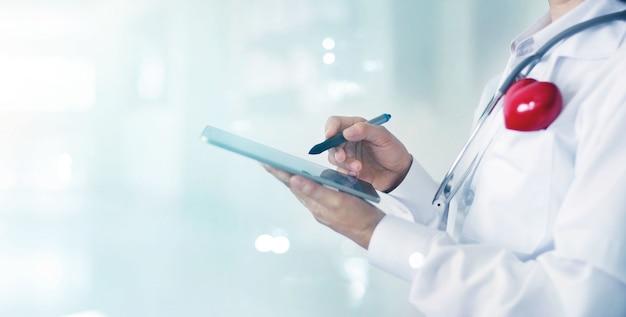 医療情報ネットワーク接続インターフェイスに触れる医師と聴診器 Premium写真