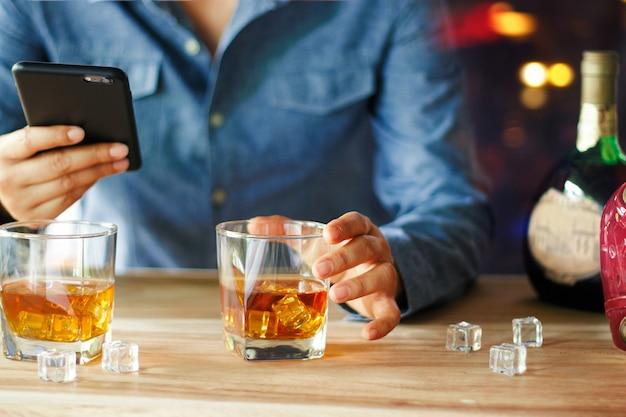 バーカウンターでウイスキーアルコール飲料を飲みながらスマートフォンを使用している人 Premium写真