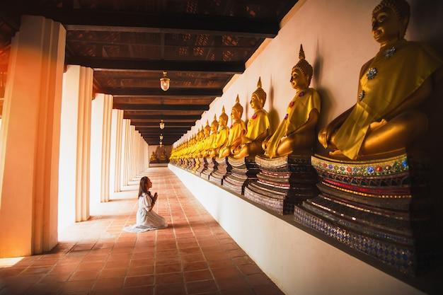 Азиатская женщина к оплате уважения к статуе будды в аюттхая, таиланд. Premium Фотографии