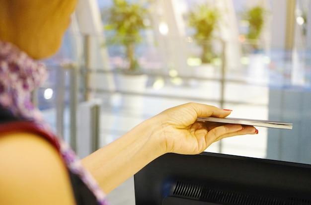 Закройте вверх по женщине при паспорта показывая на стойке регистрации в международном аэропорте. Premium Фотографии