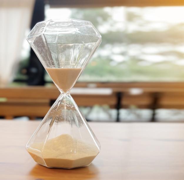 透明ガラスのない砂時計美しい、コーヒーショップのテーブルの上にあります。 Premium写真