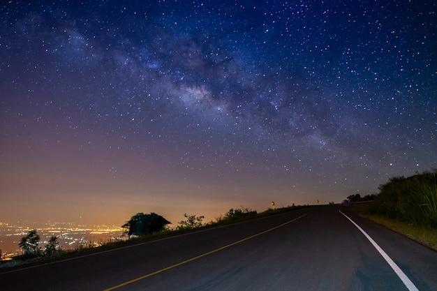 山と乳白色の銀河の背景に夜の風景の道路 Premium写真