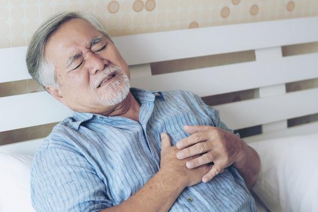 自宅で彼の胸部心臓発作の悪い痛みに苦しんでいる年配の男性のアジア人 - 年長の心臓病 Premium写真