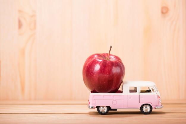 木製の床の背景を持つおもちゃの車の上のリンゴ赤 Premium写真