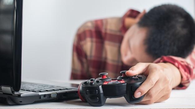 ジョイスティックのゲームパッドとラップトップを持っている手を眠っている若い男性 Premium写真