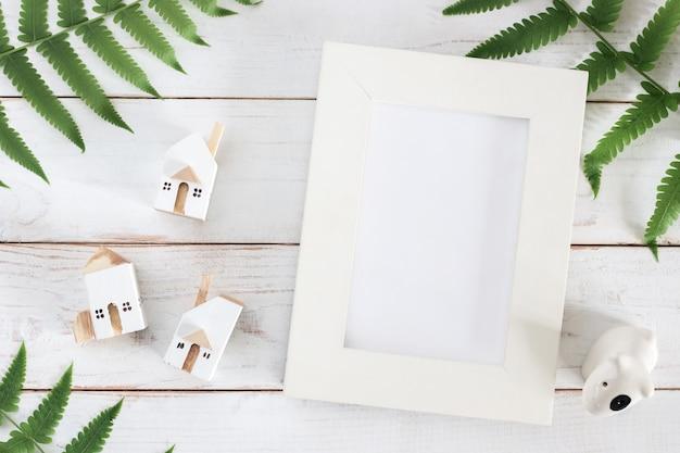 シダの葉と白い木の板の背景、ミニマリストのミニチュアの白い家モデルのモックアップ、空白の白い額縁 Premium写真