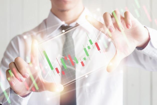 Азиатский бизнес мужчина с помощью пальца расширяет цифровой виртуальный экран с графиком подсвечник, финансовые и инвестиционные концепции Premium Фотографии