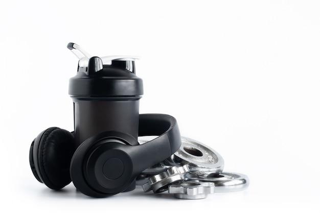 白で隔離されるヘッドフォンとクロムプレートダンベルとホエイプロテインシェーカーボトル Premium写真