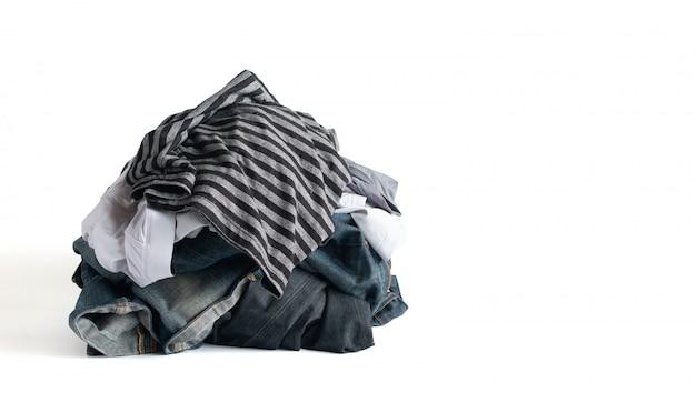 クリッピングパスと白い背景で隔離の服と色あせたジーンズパンツの山 Premium写真