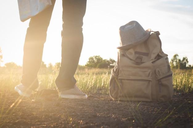 立っていると横にマップを保持しているアジア人男性の下部には、田舎の自然、太陽のレンズフレア、旅行の概念で帽子とビンテージバックパックがあります。 Premium写真