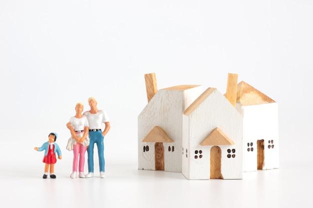 ミニチュア家族には、白い背景の上の家で父母と娘があります。 Premium写真
