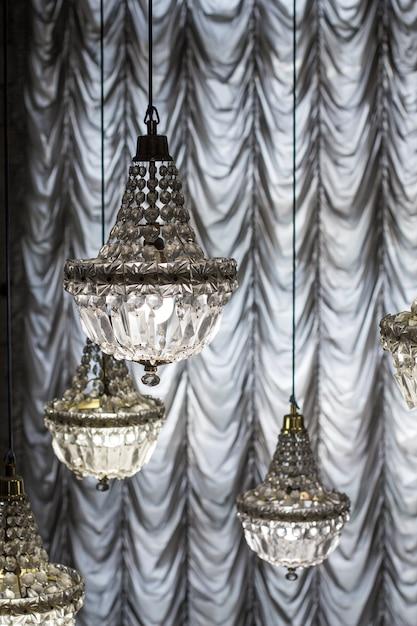Хрустальные люстры на фоне штор Premium Фотографии