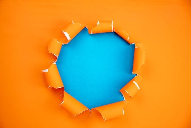 オレンジ色の青い紙の背景に開いた紙をリッピング Premium写真