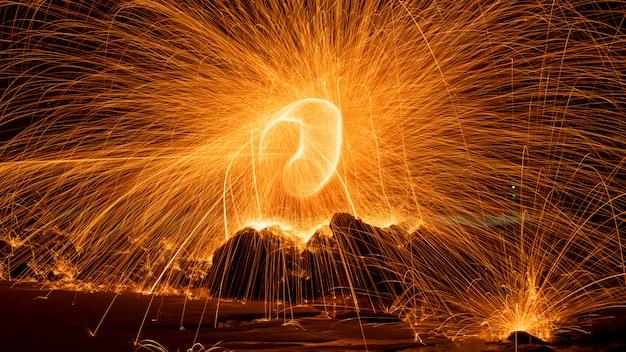 水長時間露光速度モーションスタイルで反射とスイング火旋回鋼ウール光写真 Premium写真