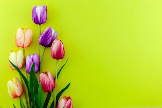 黄色の背景にマルチカラーチューリップの春の花、フラットは母の日、バレンタインデー、女性の日のホリデーグリーティングカードの画像を置く Premium写真