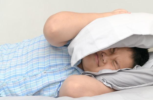 あまりにも大きな迷惑な騒音が彼の上を保持するため、枕で頭をカバーしてベッドに横たわって肥満脂肪男の子 Premium写真