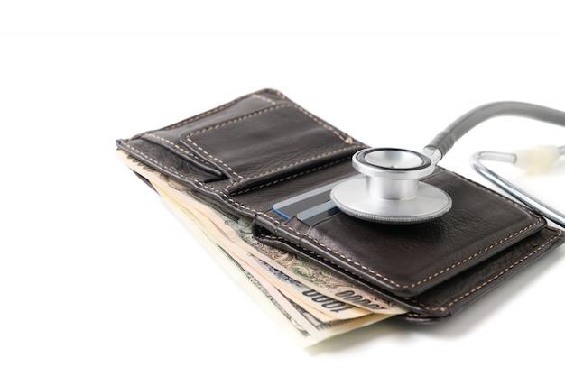 白い背景で隔離の財布に聴診器。 Premium写真