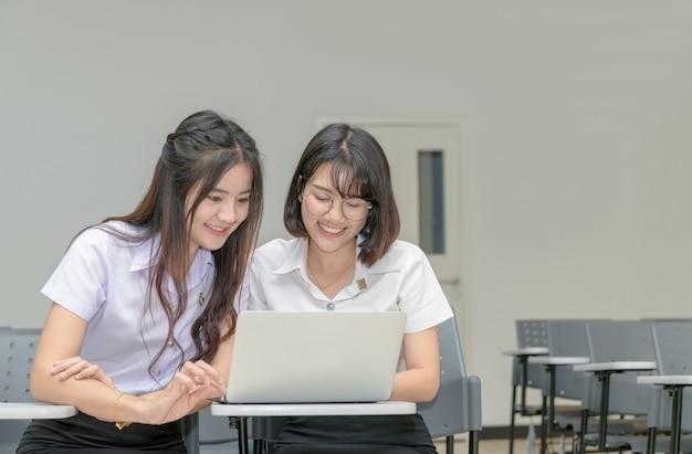 ノートパソコンを扱う制服を着たかわいい学生 Premium写真