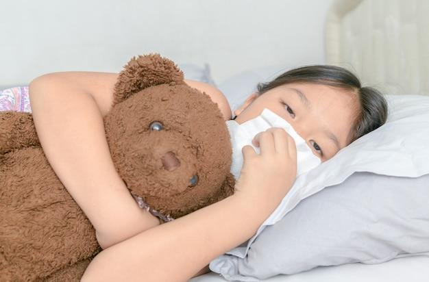 アジアの女の子がティッシュで鼻をかむ Premium写真