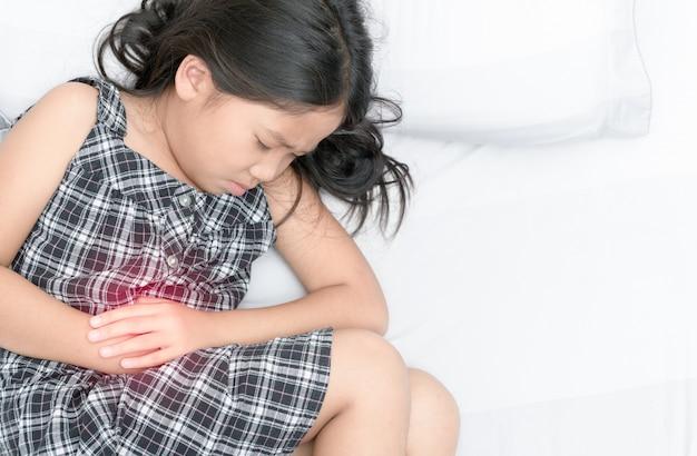 腹痛に苦しんでいるアジアの女の子 Premium写真