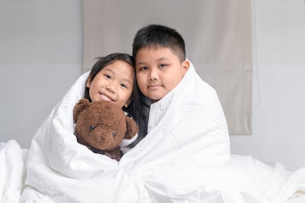 Брат обнимает сестру под одеялом Premium Фотографии