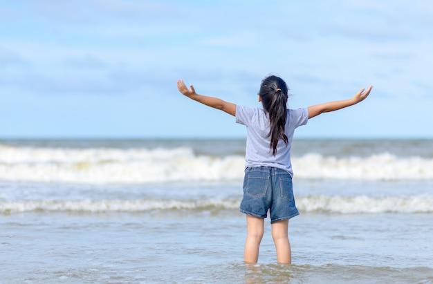 海の上の開いた手で自由を楽しんで幸せな女の子、 Premium写真