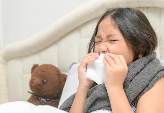 アジアの少女は鼻水があり、組織に鼻を吹きます Premium写真