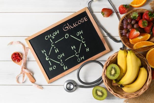 混合新鮮な果物と黒板にグルコース分子 Premium写真