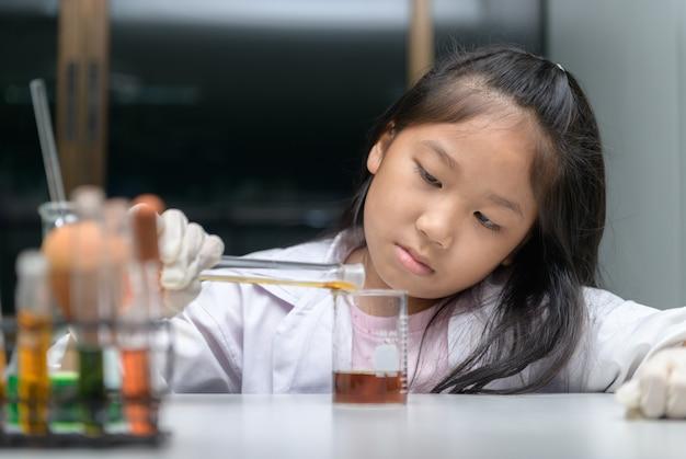 Счастливая маленькая девочка носить лабораторный халат, делая эксперимент Premium Фотографии