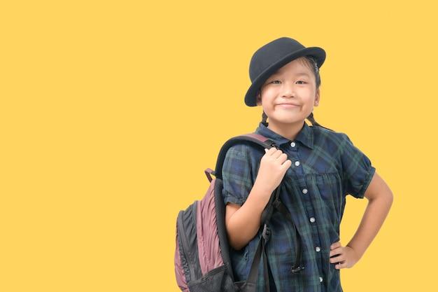 旅行に笑顔とバックパックを保持している帽子をかぶってかわいい女の子 Premium写真