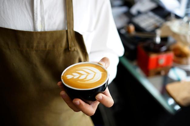 コーヒーのラテアートを作るバリスタ。 Premium写真