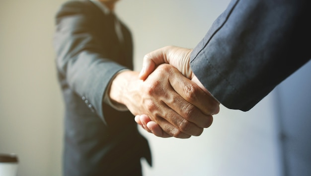 Деловые люди пожимают друг другу руки, успех Premium Фотографии