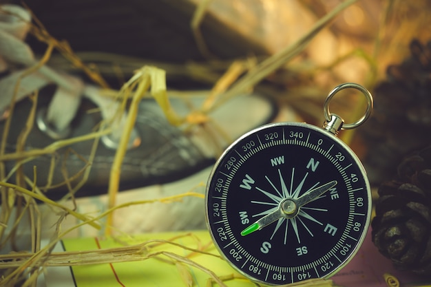 スニーカーと松の花のコンパスと紙の地図は、朝の日差しの中で乾いた麦わらの上に置かれます。 Premium写真
