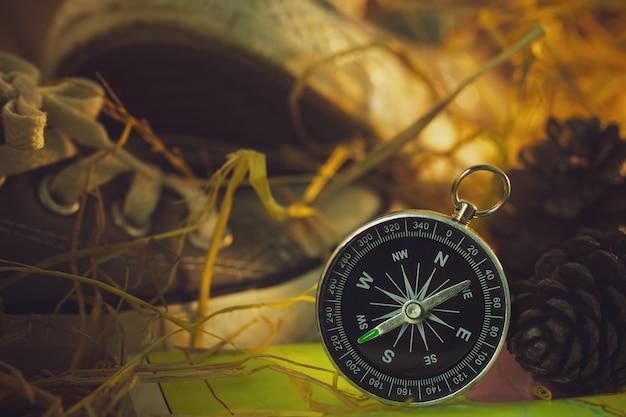 スニーカーと松の花のコンパスと紙の地図は、朝の日差しの中で乾いた麦わらの上に置いた。 Premium写真
