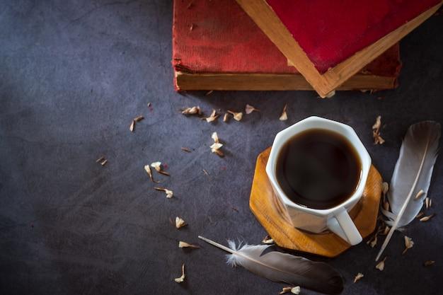 大理石のテーブルと朝の日差しの上に置かれた白いカップと羽毛とドライフラワーの花びらを持つ古い本のブラックコーヒー。 Premium写真