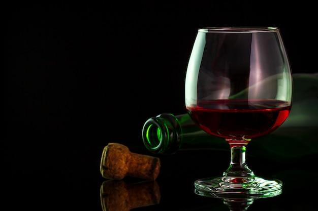 ガラスと闇の背景でテーブルの上の瓶に赤ワイン。 Premium写真