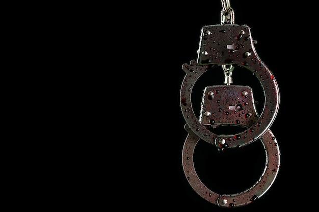 手錠をかけられ、暗闇の中で偽の血の滴 Premium写真
