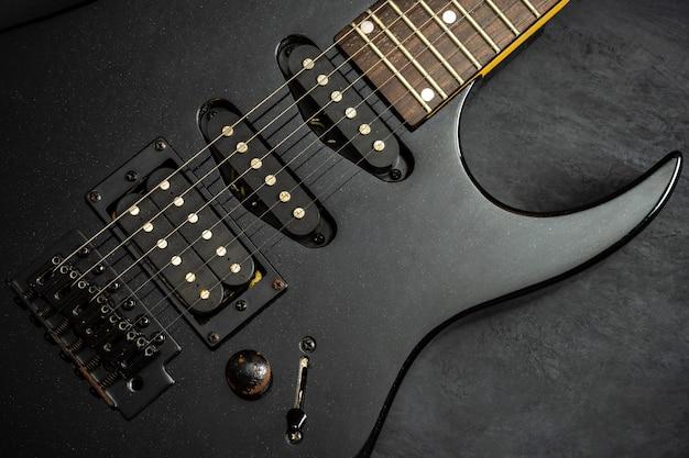 黒いセメントの床に黒いエレキギター。上面図とコピースペース。ロックミュージックのコンセプトです。 Premium写真